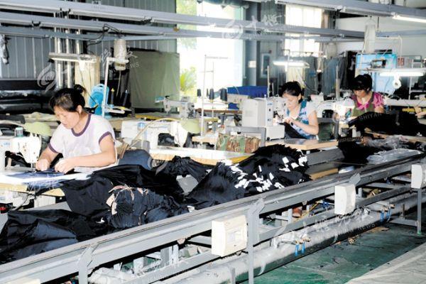 工人们正在赶制一批秋款服装